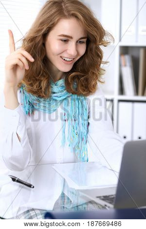Young brunette business woman working with laptop in the office. It is an idea