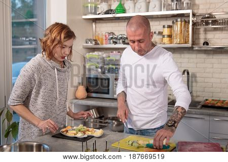 Portrait of husband and wife cooking together in the kitchen