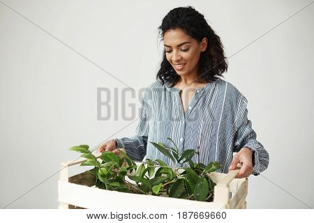 Beautiful african girl botanist smiling holding box with plants over white background. Copy space.