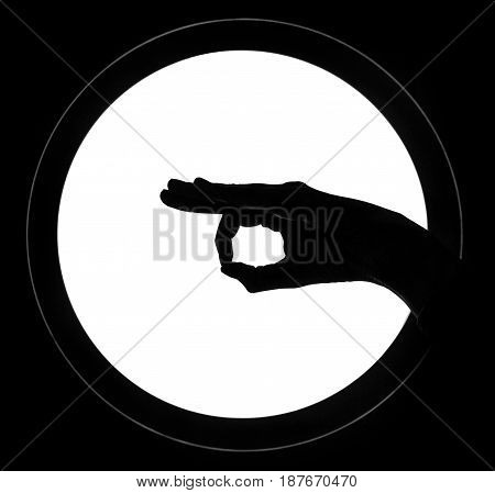 Silhouette of a hand holding something with two fingers.