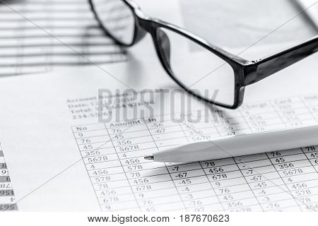 accounting work space with glasses, profit and tables on stone desk background close up