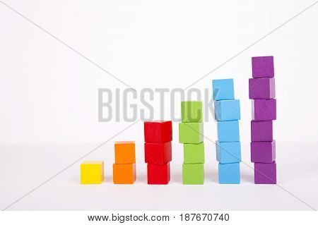 Stacks of multicolored toy blocks on white background