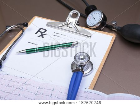 RX prescription, stethoscope, blood pressure meter and pen on white background