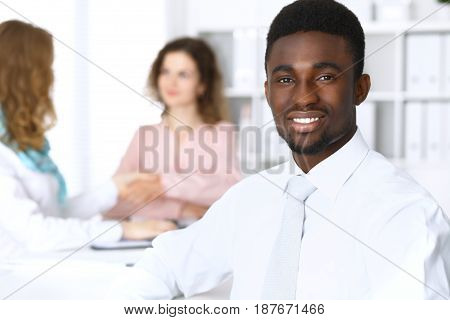 African american businessman at meeting in white colored office background.