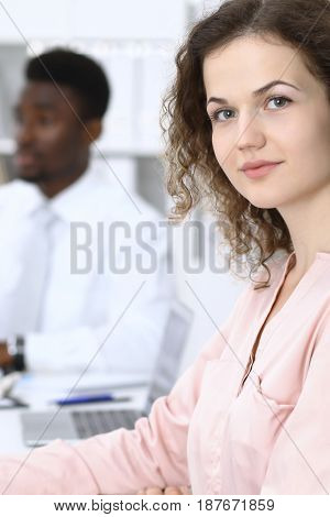 Beautiful business woman at meeting in white colored office background.