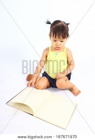 Portrait of little cute baby girl reading book on a white background