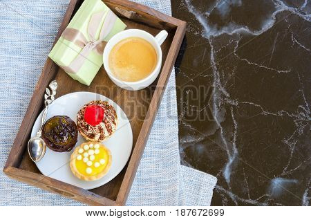 Cup of coffee with cute sweet cakes and gift box with bow on wooden tray. Woman morning breakfast surprise concept.Top view.Copy space.