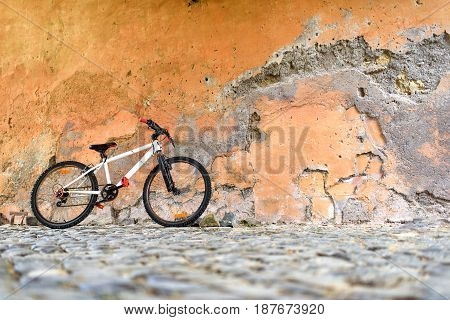 White Bicycle near a stone wall, without a bicyclist