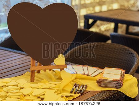 Large Brown Heart On The Table Next To The Little Yellow Hearts For The Wishes Of The Guests.  Writi