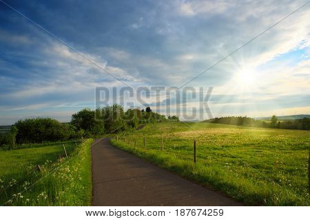 Summer country road and field on the background of the blue beautiful cloudy sky.
