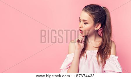 Surprised beautiful young woman in pink mini dress posing with hand on chin and looking away. Copy space