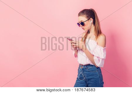 Beautiful young teenage girl in sunglasses, pink shirt, blue jeans and headphones listening music standing on a pink background