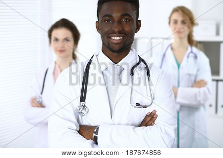 Happy african american male doctor with medical staff at the hospital.
