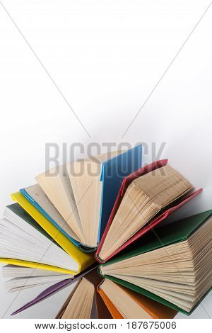 Top view of colorful hardback books in a circle. Open book, fanned pages. Back to school copy space. Education background