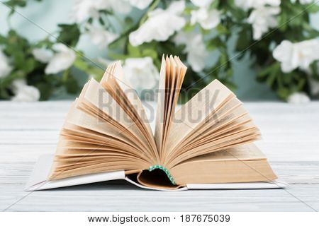 Open book, hardback books on wooden table on natural background . Back to school. Copy space for text