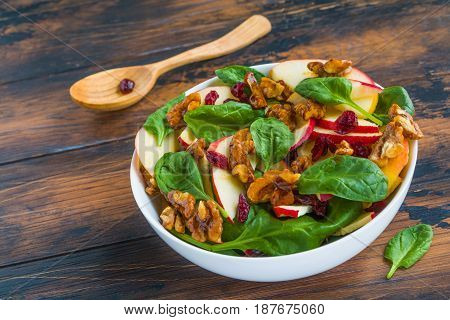 Fruit salad with fresh apples dried cranberries spinach and walnuts in a white bowl on the rustic wooden table.