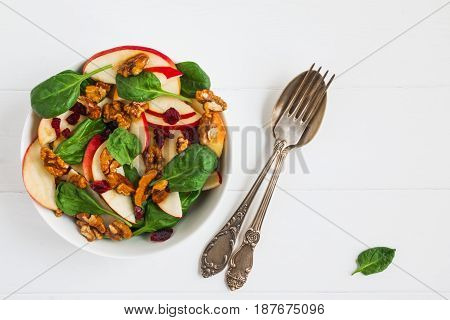 Healthy vegetarian salad with green spinach leaves dried cranberry red apple and walnuts caramelized in honey in a white bowl on the wooden table top view.