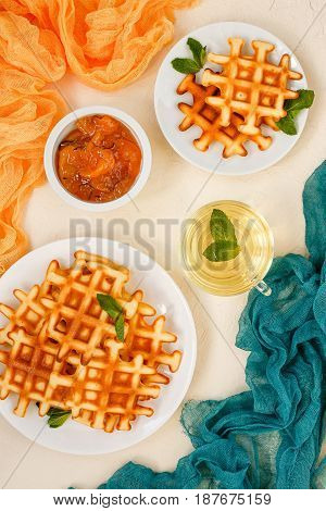 Belgian waffles on plates garnished with mint leaves glass Cup with green tea with mint and peach jam with rosemary in small bowl on beige background. Top view