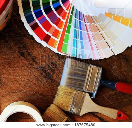 various painting tools and color palette on wooden background .