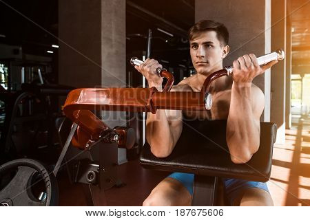 Tense muscles of hands under load. Man doing exercise for biceps in the gym. Work on tell muscles on the simulator. Photos for sporting magazines, posters and websites. sun flare
