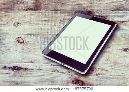 Tablet computer with blank screen on wooden background.