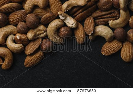 Variety Of Mixed Nuts - Almond, Hazelnuts And Cashew - On The Dark Slate Background With Copy Space.