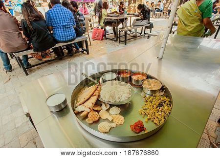 BANGALORE, INDIA - FEB 14, 2017: Students eating indian vegeterian food thali in outdoor cafe on February 14, 2017. With population 8.52 million Bangalore is the third most populous indian city
