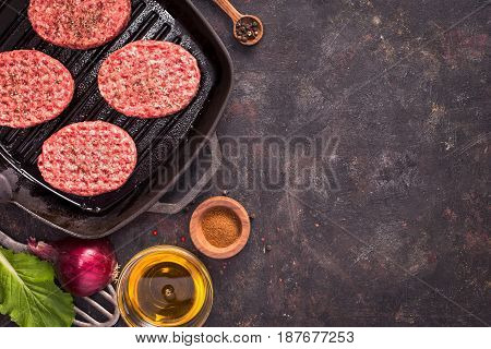 Raw beef meat steak cutlets on grill pan with oil and spices on grunge background top view with copy space