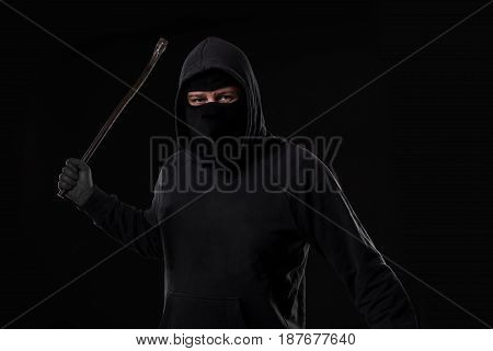 Male offender masked with a scrap. On black background at the studio. Breaking. A crime. Bandit and thief