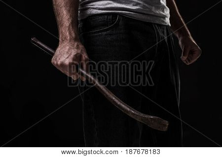 Male offender with a scrap. On black background at the studio. Breaking. A crime. Bandit and thief