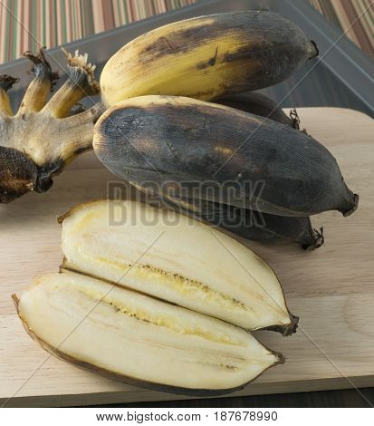 Fruits A Bunch of Black Rotten Wild Banana Asian Banana or Cultivated Banana on A Wooden Cutting Board.