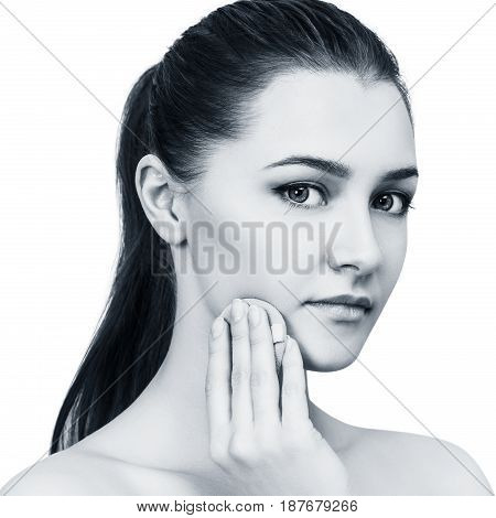Young woman applying cosmetics powder with sponge isolated on white background.