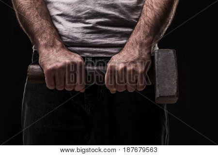 Male offender with a big hammer. On black background at the studio. A crime. Bandit and thief