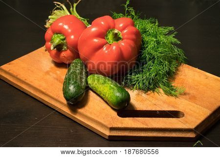 Fresh cucumbers red pepper bunch of dill on a wooden cutting board.