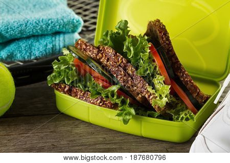 Healthy Life Sport Concept. Sneakers with Tennis Balls Healthy Sandwich on Wooden Background. Copy Space.