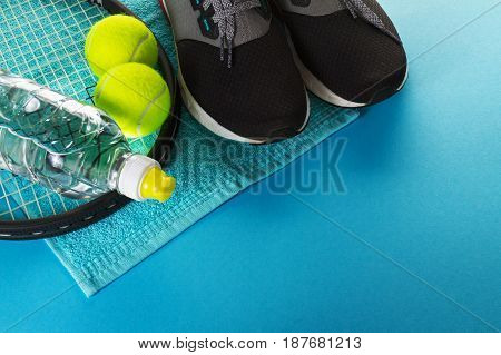 Healthy Life Sport Concept. Sneakers with Tennis Balls Towel and Bottle of Water on Bright Blue Background. Copy Space.