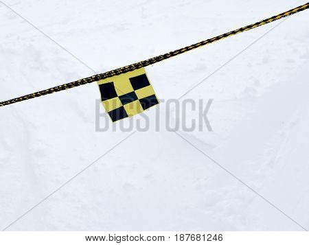 Avalanche danger flag on rope intending to barr the way for safety reasons. Yellow black chessboard.