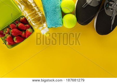 Healthy Life Sport Concept. Sneakers with Fruits Towel and Bottle of Water on Wooden Background. Copy Space.