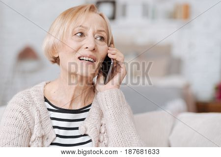 Hi there. Nice pleasant enthusiastic lady spending time at home and communicating with her acquaintance while sitting on a sofa in a living room
