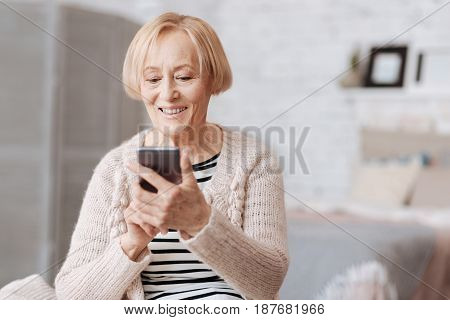 Modern hobby. Good looking cheery savvy woman enjoying her free time at home while sitting on a couch and using her gadget