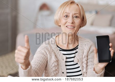Useful and entertaining. Emotional excited mature woman sitting on a sofa and showing her new smartphone while holding her thumb up