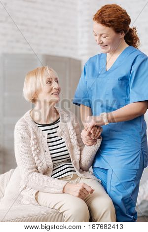 Pleasant helper. Lovely private medical worker holding her patient by the wrist and estimating the heart rate while conducting a general checkups at ladies apartment
