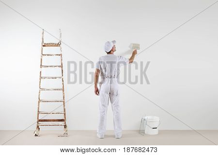 Rear view of painter man looking and painting blank wall with paint brush bucket and wooden ladder isolated on white big space