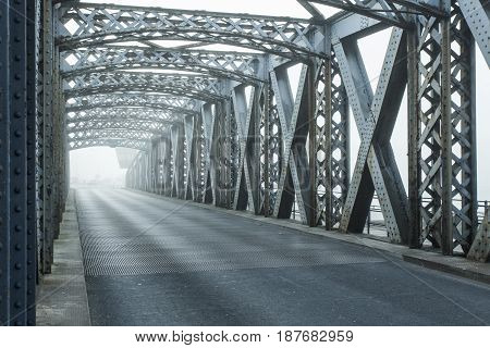 Metal Construction Of The City Bridge On A Foggy Day In Dieppe, France. Empty Asphalt Road In The Tu