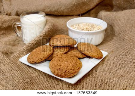 Oatmeal cookies with milk and oatmeal flakes on burlap