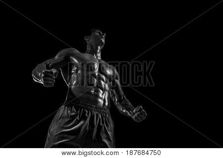 Muscular and fit young bodybuilder fitness male model posing over black background. Studio shot on black background. Black and white, b w