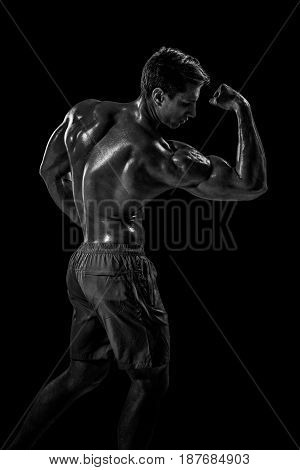 Strong Athletic Man Fitness Model posing back muscles, triceps over black background. Studio shot on black background. Black and white, b w