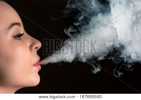 The face of vaping young woman on black studio background