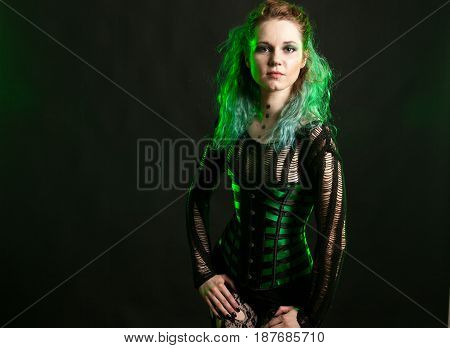 Sexy Woman in cosplay corset posing in studio with a green light from behind. Studio photo. Fashion and cosplay