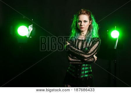 Fashion Woman in cosplay corset posing in studio with a green light from behind. Studio photo. Fashion and cosplay